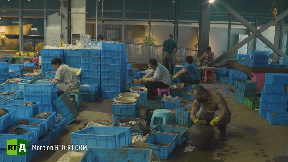 At the Maritime Silk Road Museum in China, archaeologists are handling crates with silt and ceramics. Still taken from RTD documentary Yangshan City Port in the 'This is China' series.