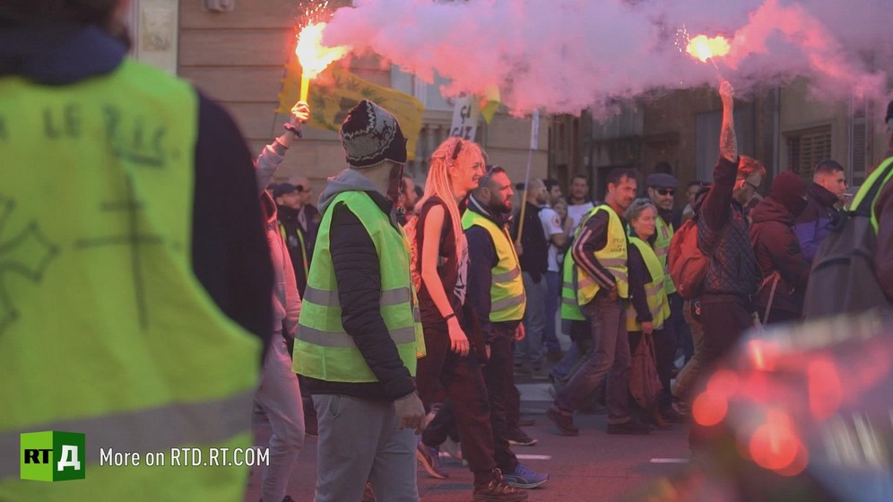 People holding flares and marching during a Yellow Vest demonstration in Toulouse, France. Still taken from RTD documentary Yellow Vest Fever.