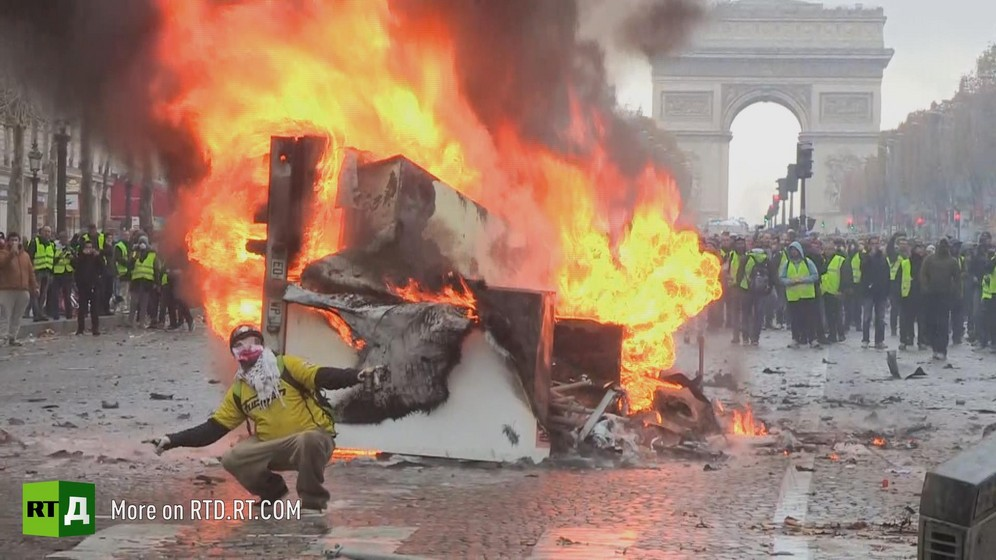 a Yellow Vest protestor wearing a mask  is crouching in front of a burning car, arms outstretched. In the background, a crowd of demonstrators wearing yellow vests are walking in front of the Arc de Triomphe in Paris. Still taken from RTD documentary Yellow Vest Fever.