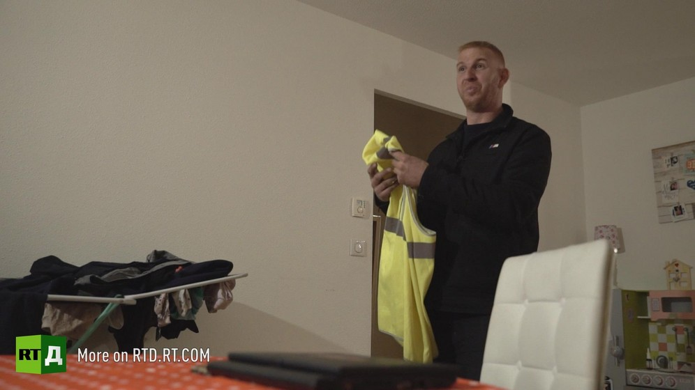 At home, Ghislain Coutard shows the hi viz yellow vest he used in the viral facebook video that started the Yellow Vest protest movement in France. Still taken from RTD documentary Yellow Vest Fever.