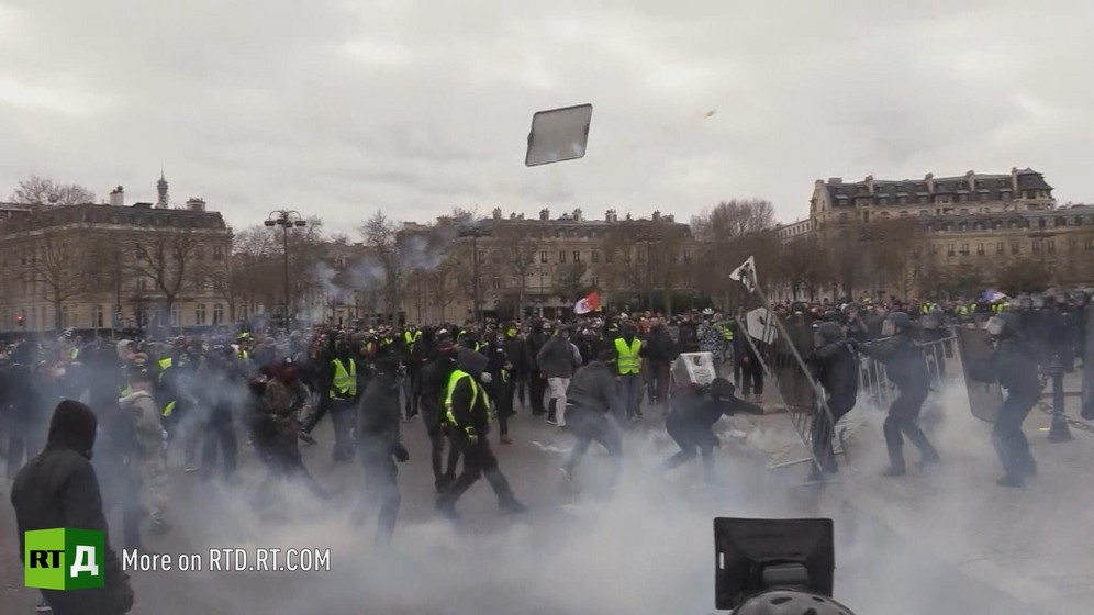 A barrier thrown by protesters is flying mid air at the Arc de Triomphe in Paris during a Yellow Vest protest.
