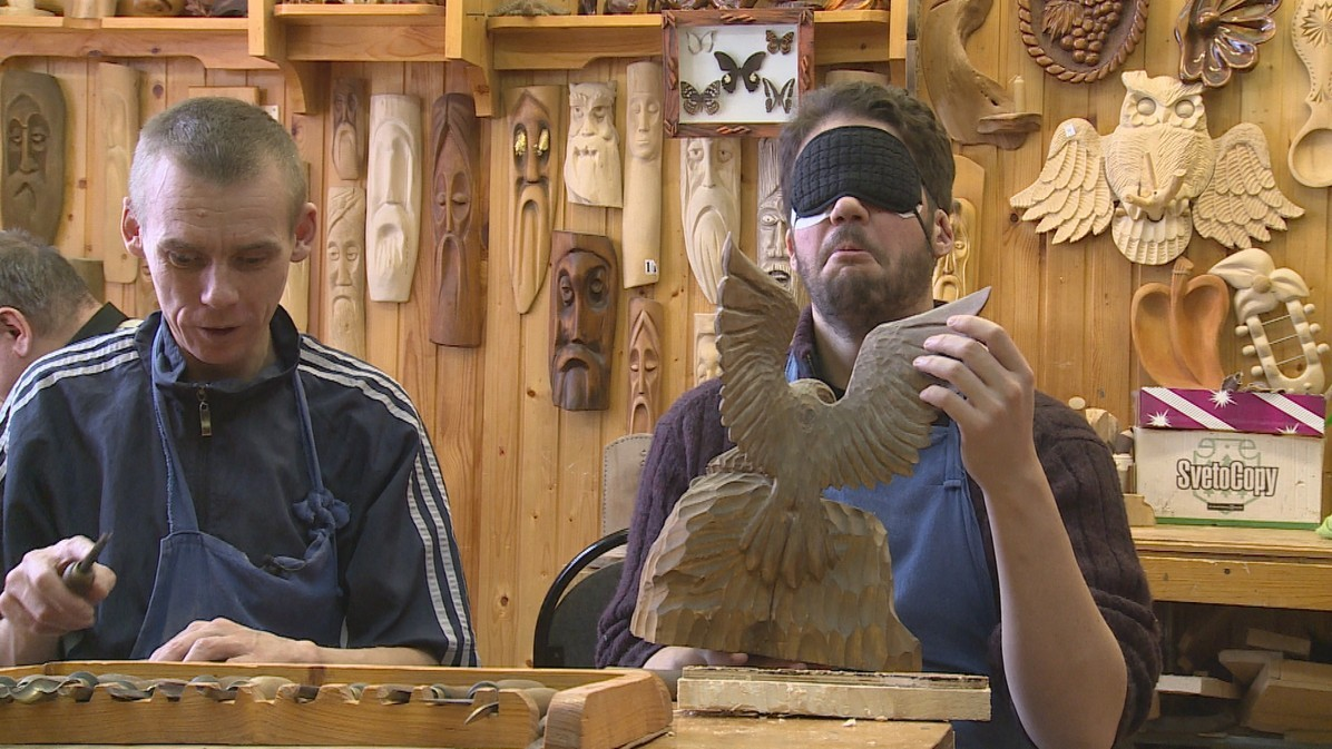 James and Sergey try wood carving at the rehabilitation centre.
