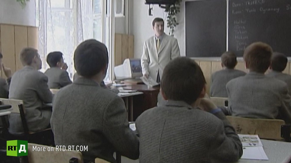 Boys in grey uniform are sitting in a classroom facing their teacher in a lab coat. Still taken from RTD's documentary series The Gulen Mystery.