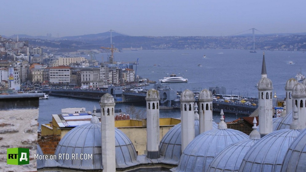 The Bosphorus in Istanbul, Turkey. In the foreground are the grey-blue domes and minaret of a mosque, then a ship next to the bank, with a bridge, the water and opposite bank of the straits in the background. Still taken from RTD's documentary series The Gulen Mystery.
