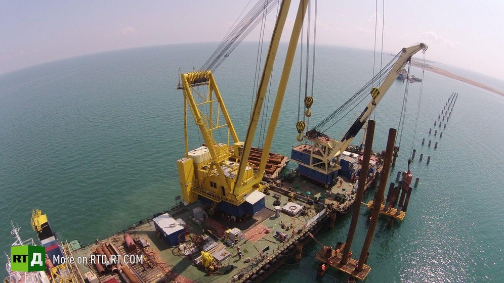 Building of Crimea Bridge, aerial view of yellow crane and sea. Still taken from RTD documentary The Bridge.