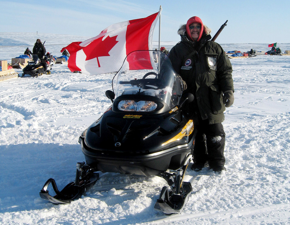 Canadian Inuit ranger stands on the snow next to his snowmobile at Resolute Bay, Canada
