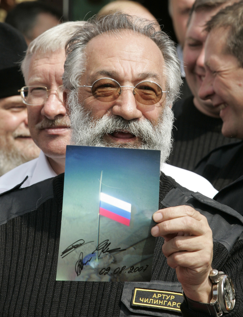 Russian Arctic explorer Artur Chilingarov holds a photograph showing the Russian flag planted on the North Pole seabed, when he returned to Moscow, Russia