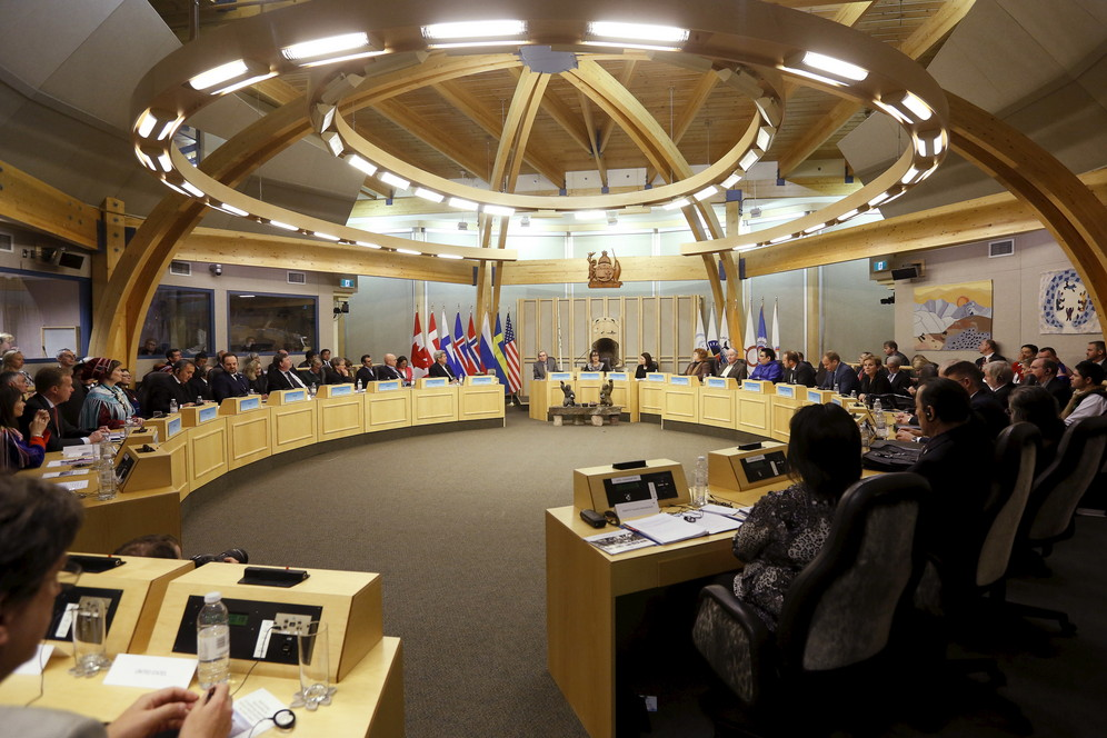 Dozens of Arctic Council delegates sit  around tables in spherical wooden building in Greenland