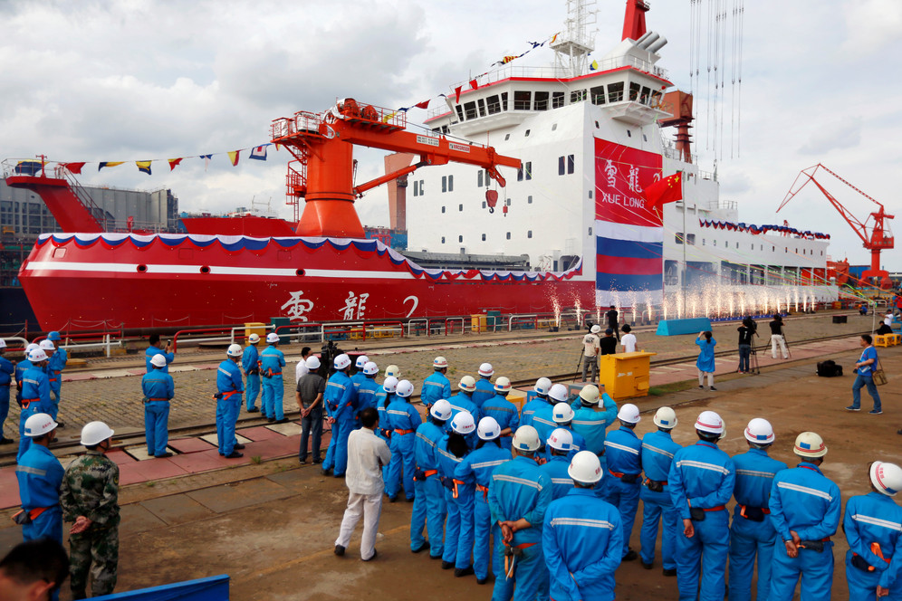People standing on dock alongside China's first polar icebreaker at launch ceremony in Shanghai, China