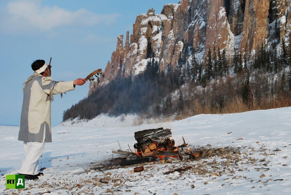 Evenk Shaman performing ritual in front of Lena Pillars, Yakutia, Russia