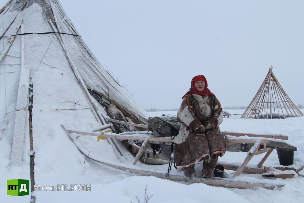 A Nenets woman on a traditional sledge and a chum