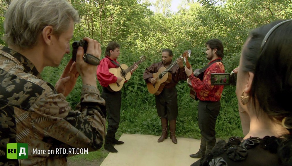 A man and a woman film Gypsy guitarists playing traditional Gypsy songs in Russia.