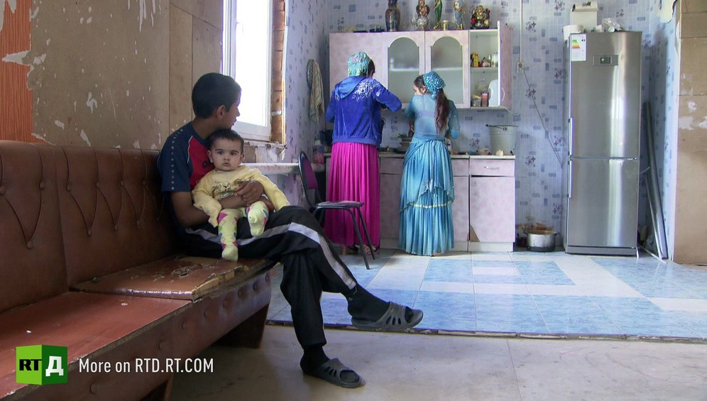 Twelve year old boy holding a baby while his young wife and mother are doing the washing up, inside a Kalderash gypsy home in rural Russia.