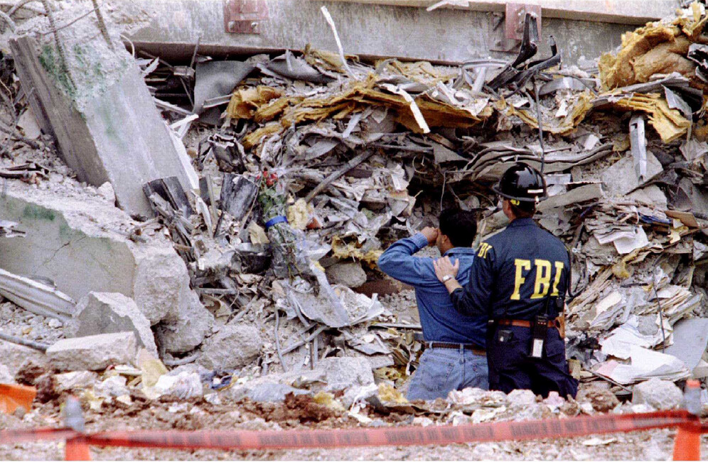 An FBI agent comforts a weeping man whose loved one was still trapped in the rubble of the bombed Murrah Federal Building in Oklahoma City, Oklahoma, U.S. May 5, 1995