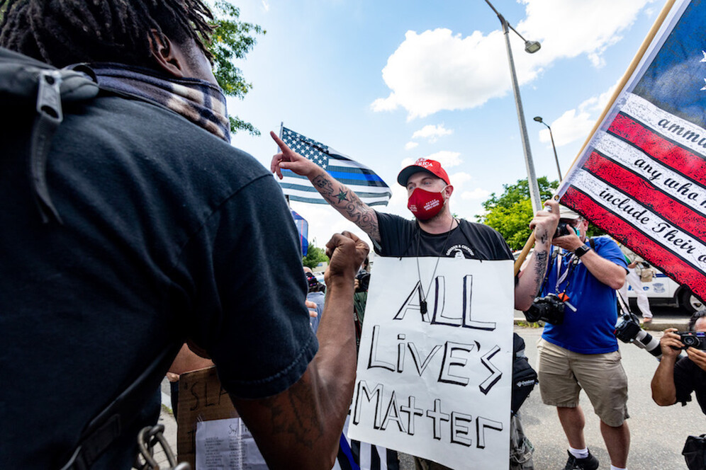 "A man wearing a sign ""All lives matter"" with a Three Per Cent Militia flag and Trump hat, argues with people who attend a Juneteenth rally in Boston. Juneteenth commemorates when the last enslaved African Americans learned in 1865 they were free, more than two years following the Emancipation Proclamation"