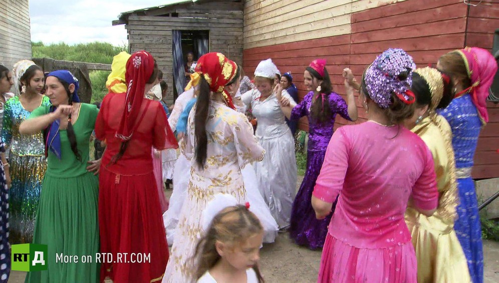Group of Kalderash Gypsy women wearing long, colorful skirts, dance together at wedding
