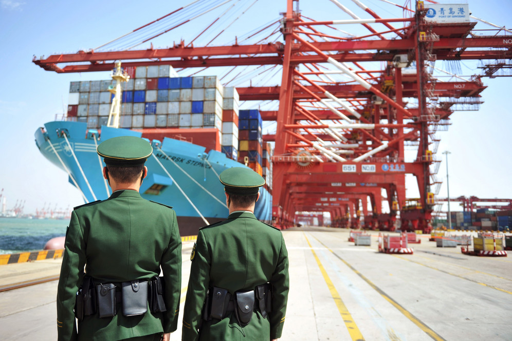 Police in front of cargo ship loading containers in China