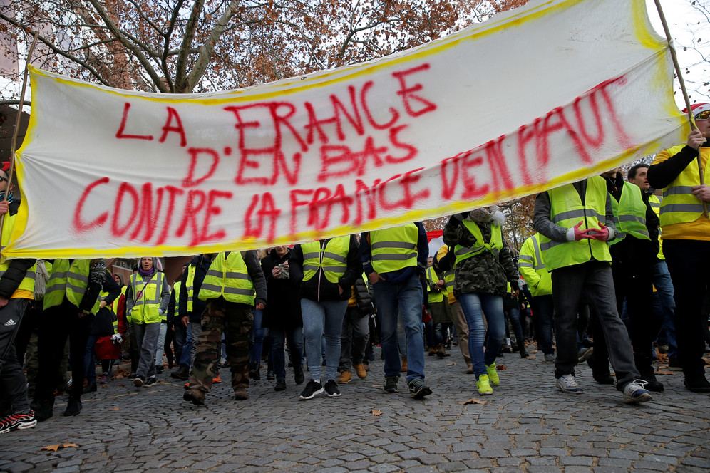 Yellow Vest Protesters holding banner that reads,