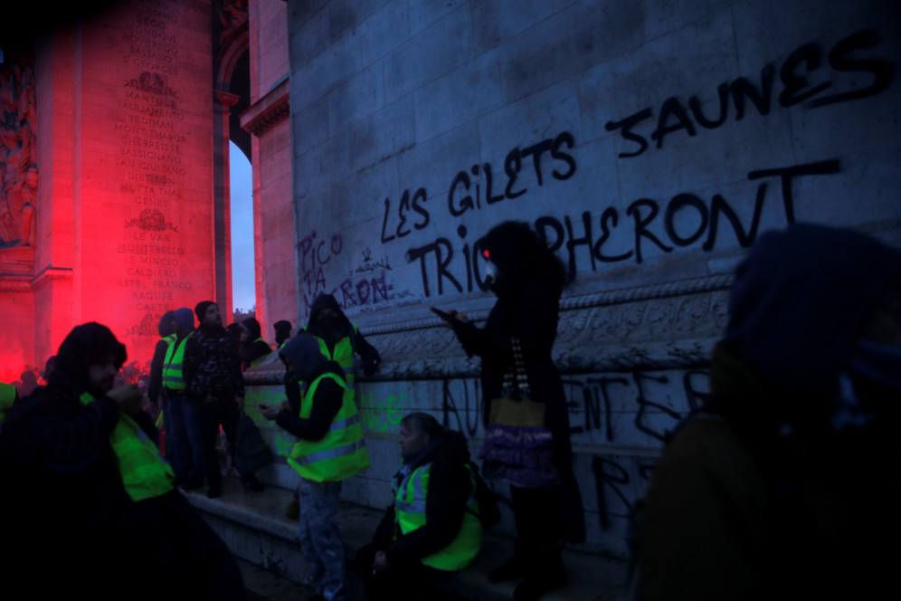 Masked protesters check their phones beneath the Arc de Triomphe painted with the slogan