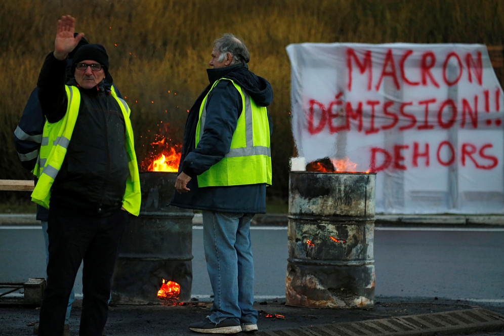Man wearing yellow vest waves, near sign saying