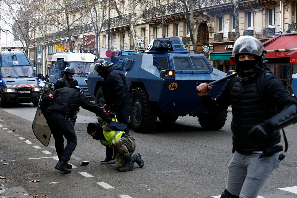 Policeman holds down a Yellow Vest protester with armoured vehicle in the background in Paris, France