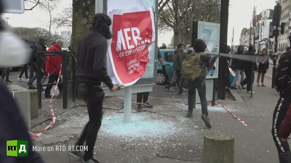 A person wearing a hoodie watches as another, also wearing a hoodie and a backpack, breaks the glass on urban furniture with an iron bar during a Yellow Vest protest in France.
