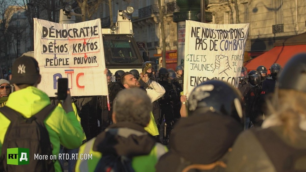 Protesters marching in Toulouse during a Yellow vest protest carrying signs about the RIC and calling Yellow Vests and police to unite. Still taken from RTD 's documentary, Yellow Vest Fever.