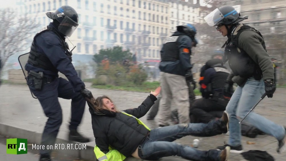 One riot policeman wearing a helmet, carrying a shield and a baton, drags a female Yellow Vest protester by the hood along the ground, while another policeman in plain clothes and wearing a helmet with the visor up towers over her, with other policemen neutralising another protester in the background.