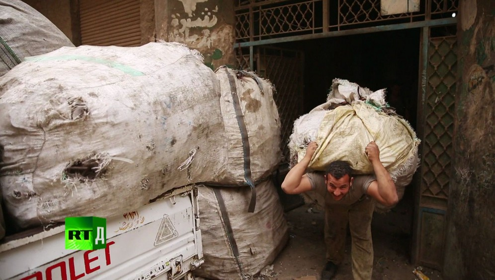 Zabbaleen Cairo rubbish collector carrying a huge bail of trash in Garbage City