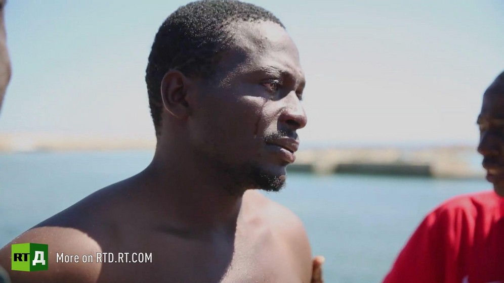 Head and shoulders of male African migrant crying after being rescued from the sea in Tunisia. Still taken from RTD documentary Fisher of Men.